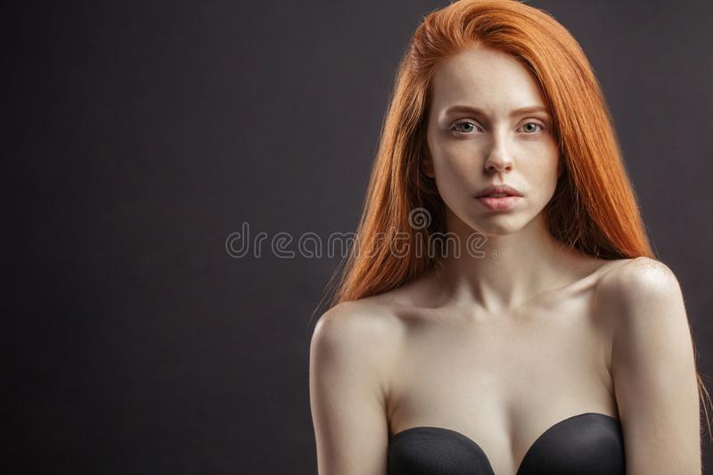 Slim young sex appealing girl with long gorgeous red hair on bla royalty free stock image