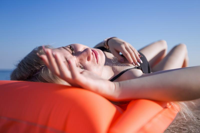 Slim young woman in swimsuit sunbathes on pink pool raft stock photography