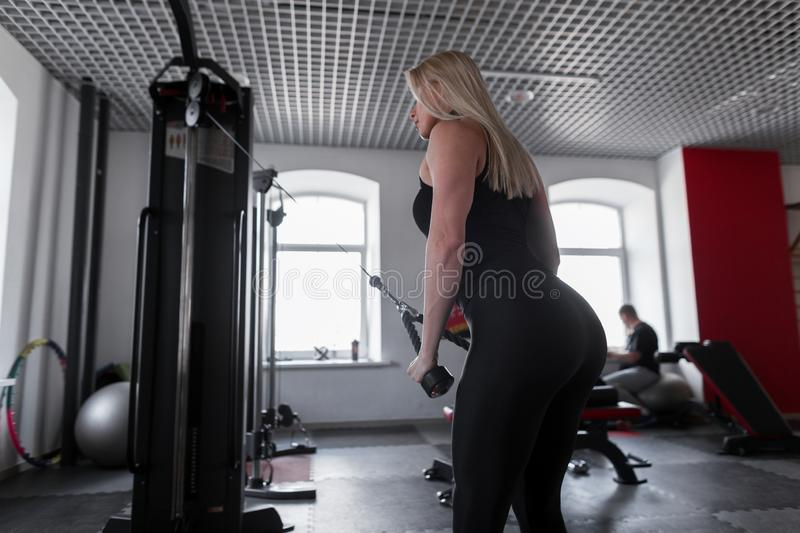 Slim young woman in trendy sportswear doing strength exercises for hands in a modern gym. Girl is engaged in fitness. stock photo