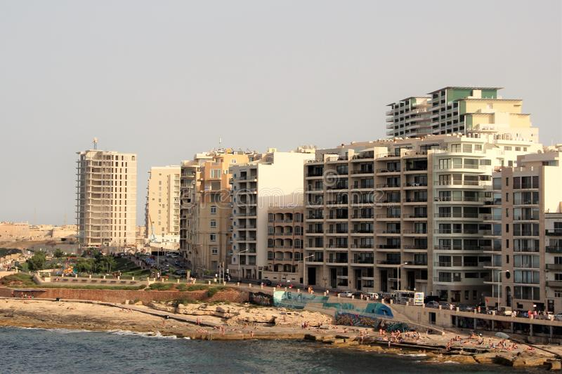 Slima, Malta, July 2014. Modern buildings on the waterfront, the beach and the people resting. stock image