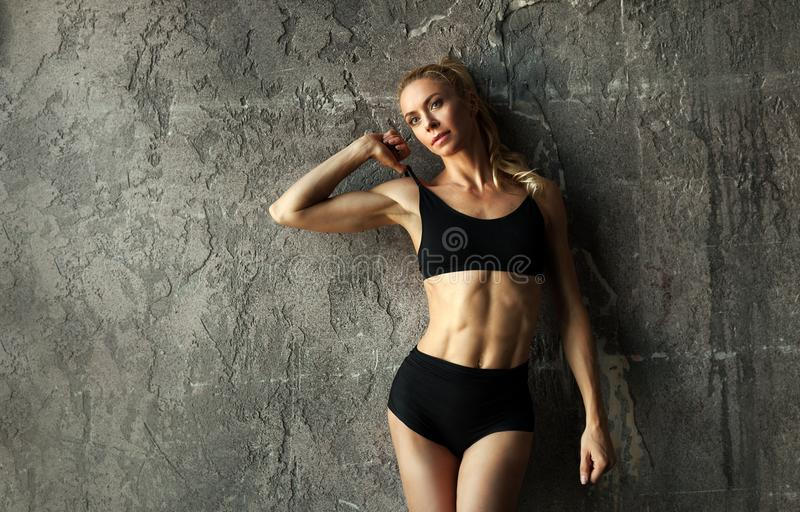 Fit female fitness model posing and showing her muscular body with strong and tanned abdominal muscles in front of concrete wall. SlimFit female fitness model royalty free stock image