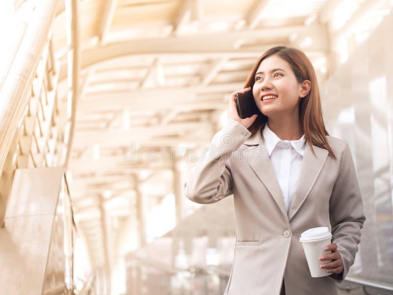 Slimme Aziatische bedrijfsvrouw in een kostuum met mobiele telefoon stock foto