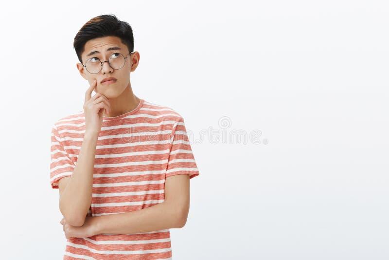 Slimme Aziatische kerel die raadsel in mening oplossen die nadenkend en ontspannen hogere juiste hoek, het denken, het maken beki stock fotografie