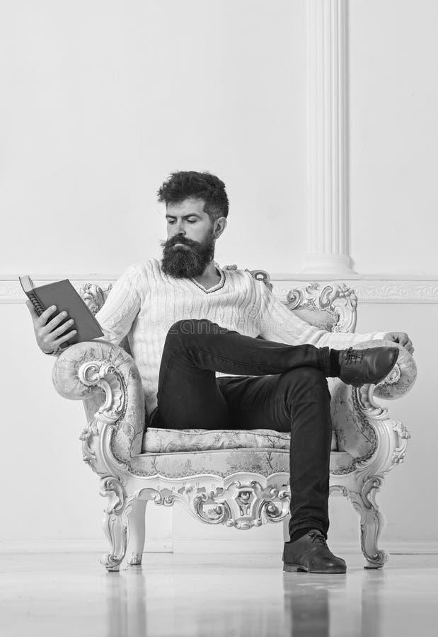 Slimme de spreker zit op leunstoel en leest boek, witte muurachtergrond De wetenschapper, professor op peinzend gezicht geniet va stock foto's