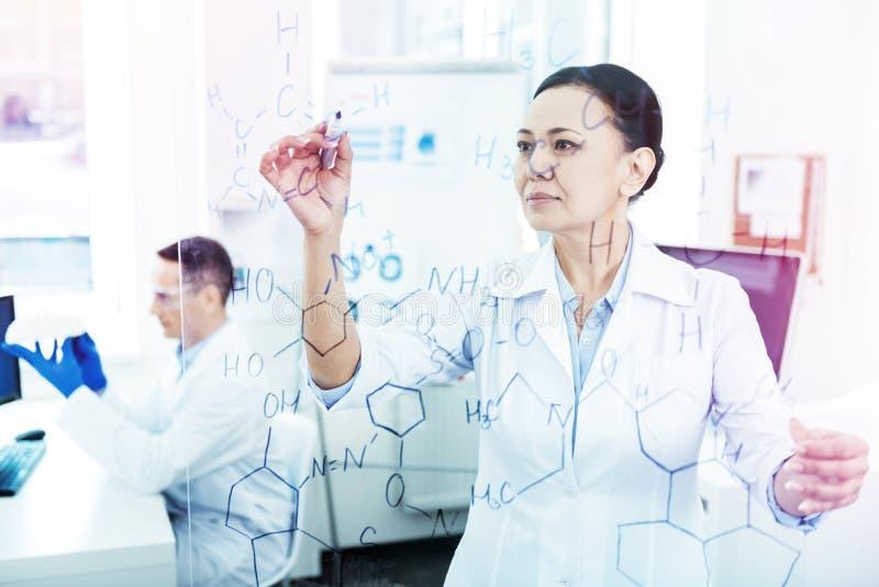 Slimme harde werkende vrouw die in het laboratorium werken stock afbeelding