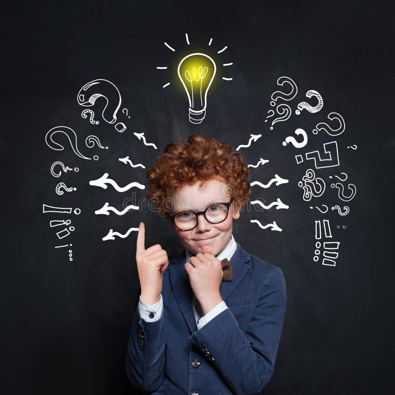 Slimme jong geitjeleerling met lightbulb Brainstorming en ideeconcept stock fotografie