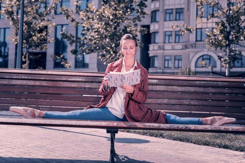 Slimme jonge ballerina die een boek in het park lezen royalty-vrije stock foto