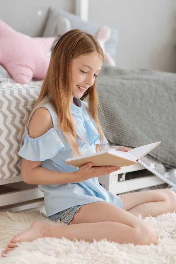 Slimme jonge damelezing in slaapkamer stock fotografie