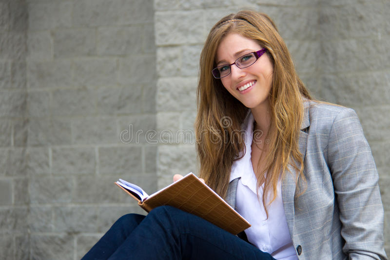 Slimme jonge jongelui die haar dagboek lezen stock foto's