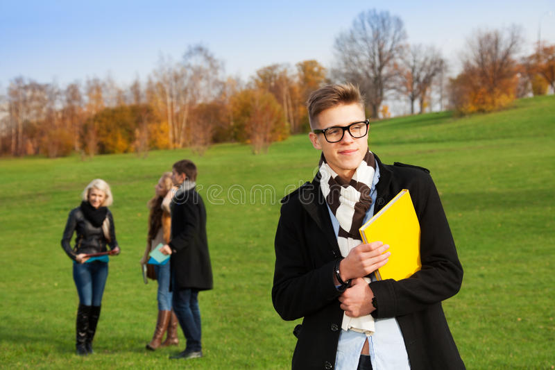 Slimme jonge mens in universiteitspark royalty-vrije stock foto's