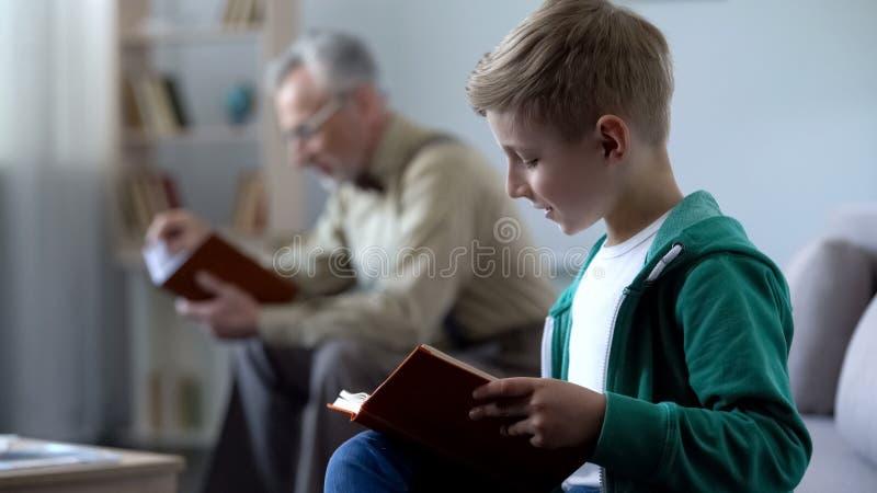 Slimme jongen en de oude boeken van de mensenlezing, betaalbaar onderwijs voor verschillende leeftijden stock foto