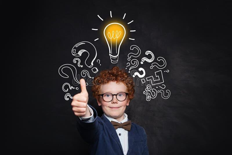 Slimme jongensstudent die duim op bordachtergrond tonen met lightbulb en vraagteken Brainstorming en ideeconcept royalty-vrije stock foto
