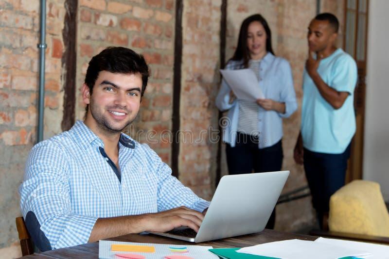 Slimme Kaukasische softwareontwikkelaar met computer op kantoor royalty-vrije stock fotografie