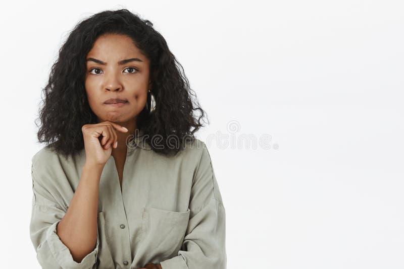 Slimme knappe modieuze Afrikaanse Amerikaanse vrouwelijke ondernemer die het betrokken en verwarde het denken smirking fronsen zi stock foto