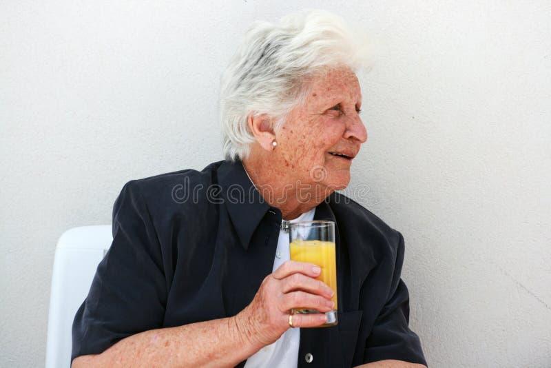 Slimme oude dame met jus d'orange stock afbeeldingen