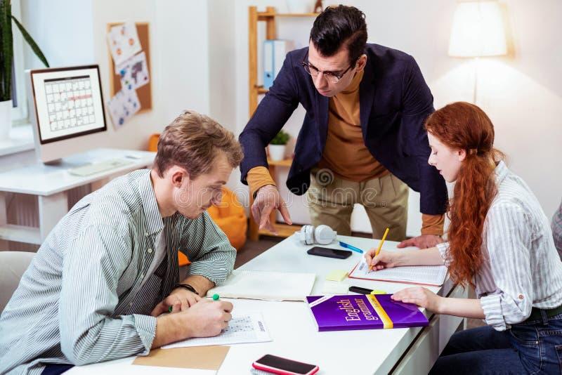 Slimme professionele mannelijke leraar die zijn studenten helpen stock foto