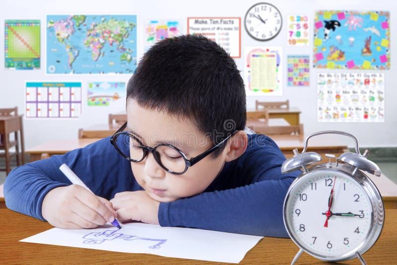 Slimme schooljongen die in het klaslokaal bestuderen royalty-vrije stock fotografie