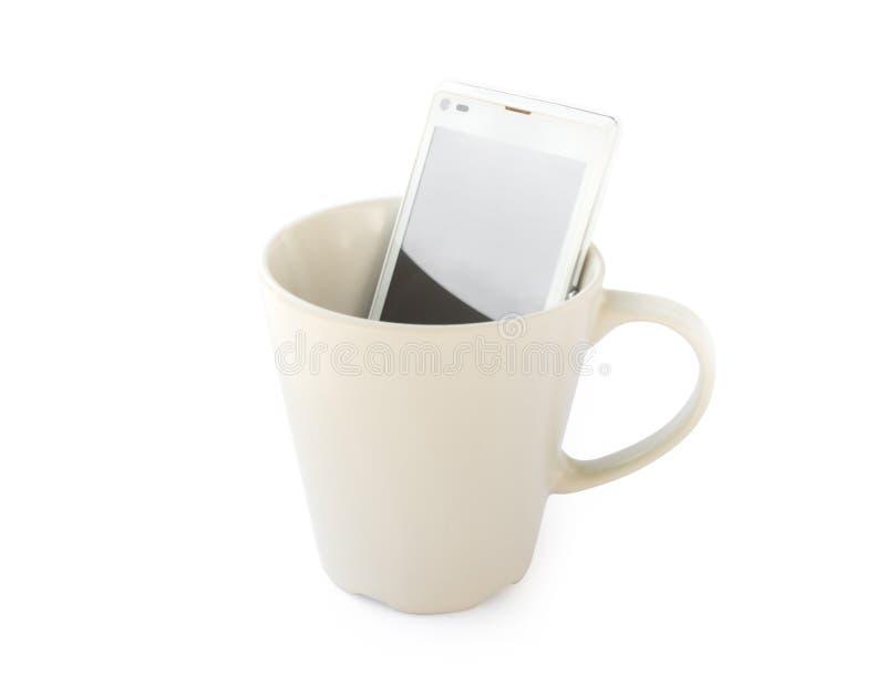 Slimme telefoon in lege mok op witte achtergrond, Ochtendontbijt stock afbeelding