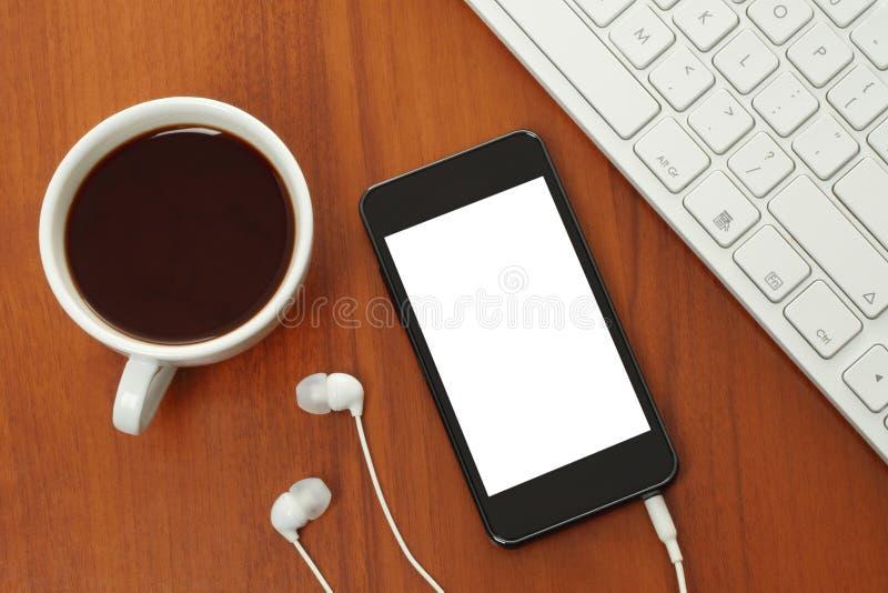 Slimme telefoon met hoofdtelefoons, toetsenbord en koffiekop royalty-vrije stock fotografie
