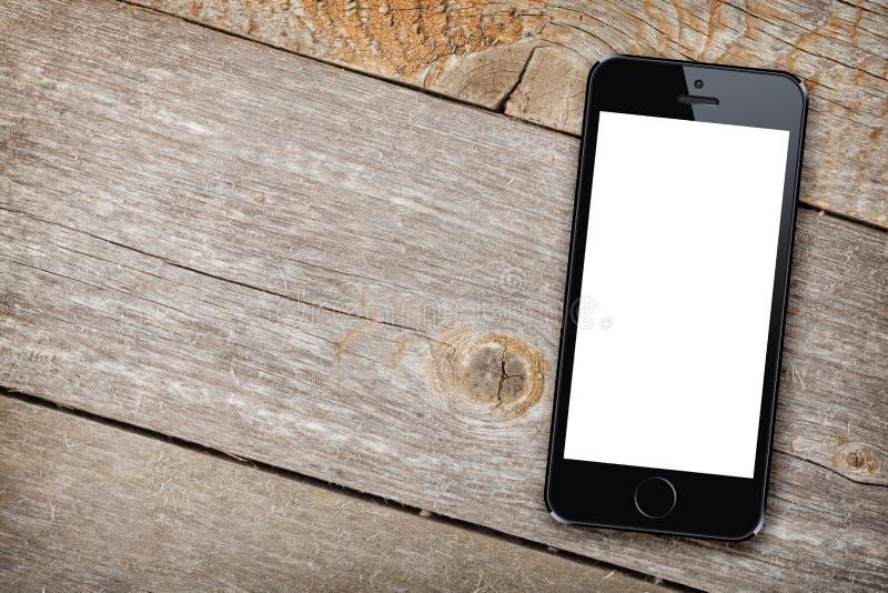 Slimme telefoon op houten lijst stock afbeelding