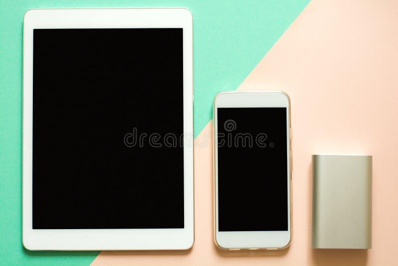 Slimme telefoon, tablet en machtsbank op document achtergrond De aanvulling van concept stock afbeeldingen