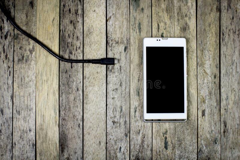 Slimme telefoonbehoefte om een batterij op houten plank te laden stock fotografie