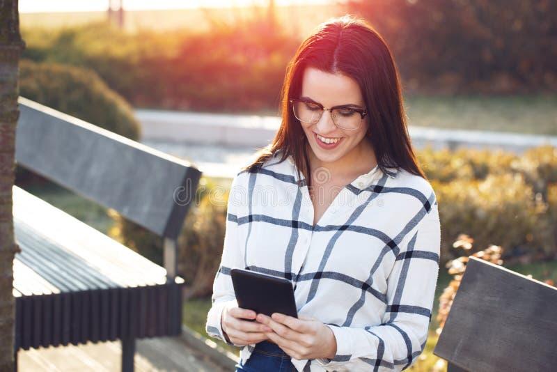 Slimme toevallige vrouw in glazen die tablet gebruiken openlucht stock foto's