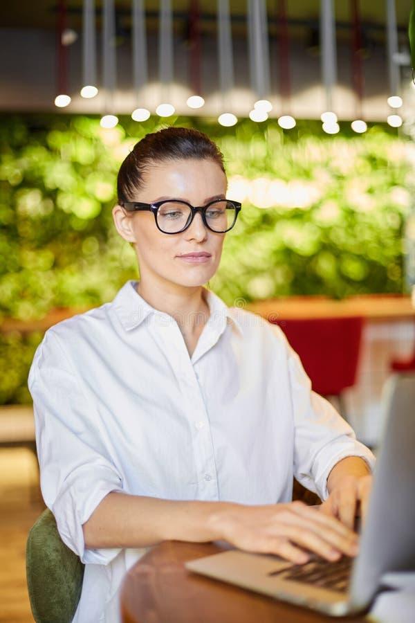 Slimme vrouw die laptop met behulp van terwijl het werken stock afbeelding