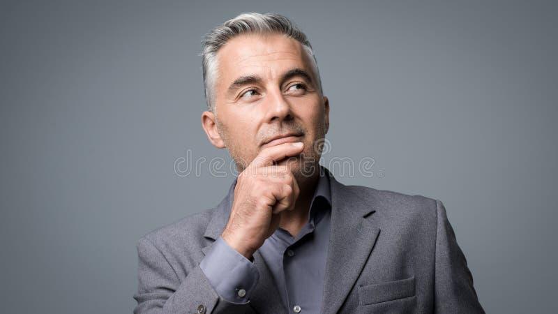 Slimme zakenman die met hand op kin denken royalty-vrije stock foto's