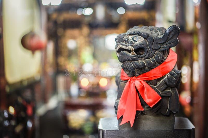 Slimme zwarte het standbeeldblik van de steenleeuw bij de rechterkant, rood litteken royalty-vrije stock foto