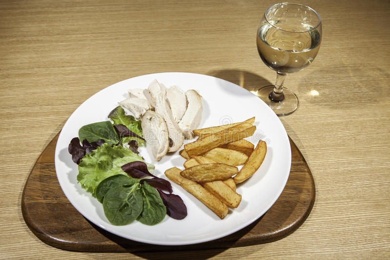 Slimmer`s chicken meal with salad, fries and wine. Small portion of a healthy meal served with hite wine stock photography
