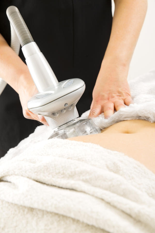 Slimming and cellulite laser treatment at clinic. Female client gets slimming and cellulite therapy with laser at professional beauty clinic royalty free stock photo