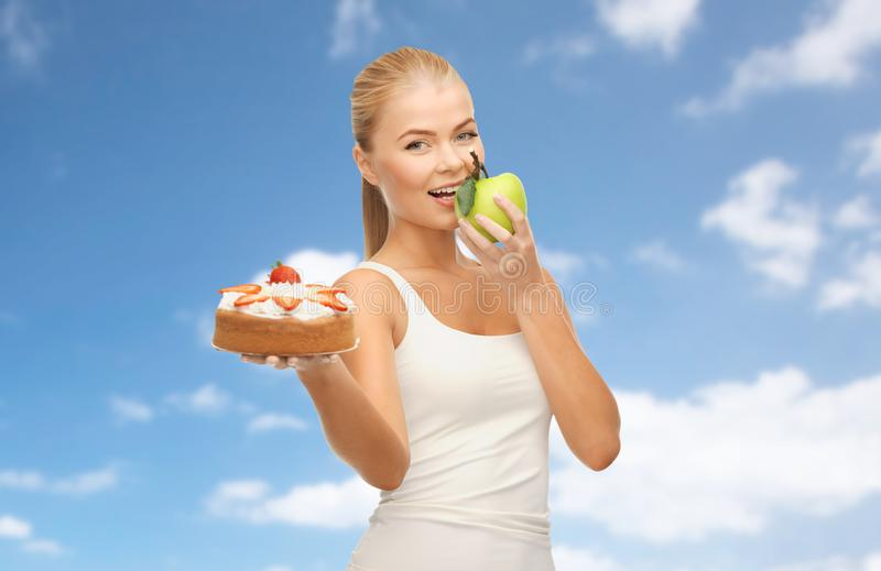 Happy woman eating apple instead of cake. Slimming and diet concept - happy woman eating apple instead of cake over blue sky and clouds background royalty free stock photos