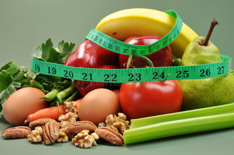 Slimming Diet Healthy Food. Group of wholesome, organic food, including pear, apple, tomato, eggs, nuts, pecans, walnuts, carrot, banana, and apple, for a royalty free stock image