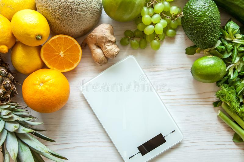 Flat lay composition with kitchen scales, healthy vegetables and fruit on wooden background. Weight loss diet royalty free stock photography