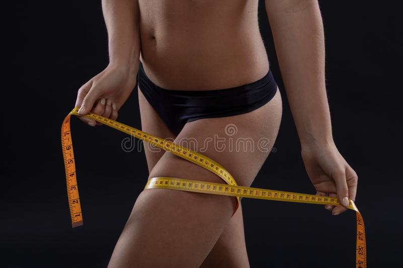 Slimming woman measuring her attractive leg on black background royalty free stock image