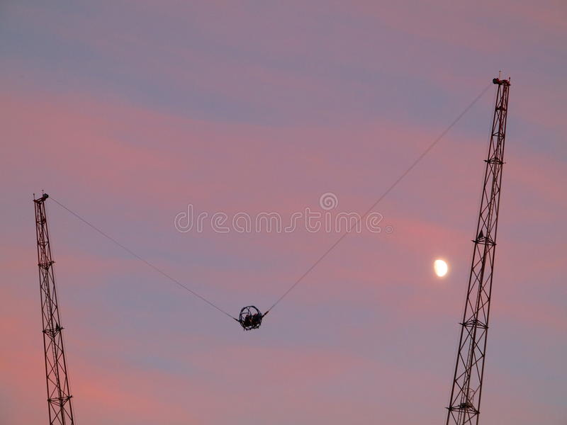 Slingshot extreme ride at dusk by moon shining. People experience the slingshot extreme ride by a pink purple sky and the moon shining stock images
