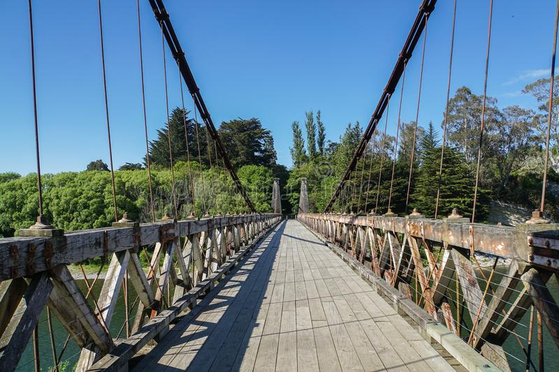 Sling wooden bridge across the river in New Zealand stock photography