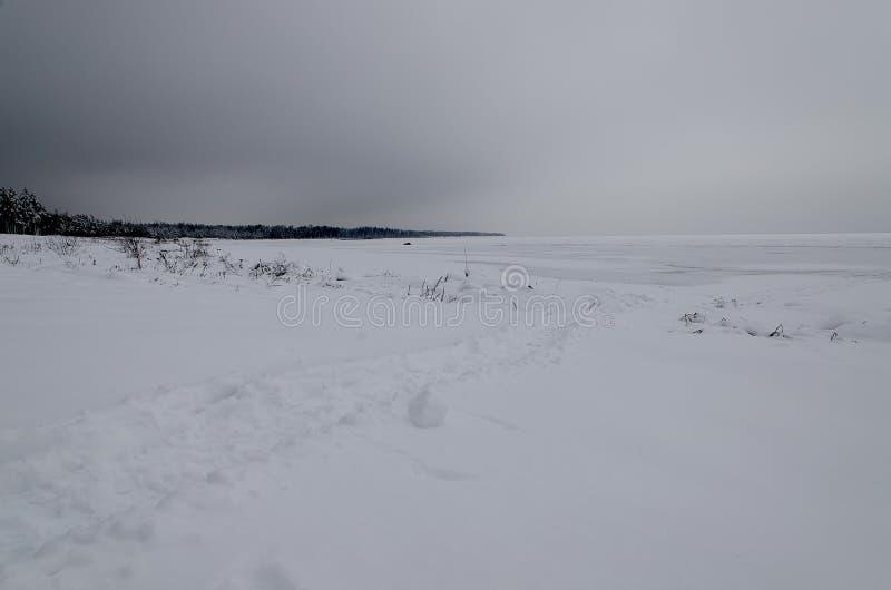Slingan i snön, som leder in i det öppna havet på en bakgrund av mörk vinterhimmel royaltyfria bilder