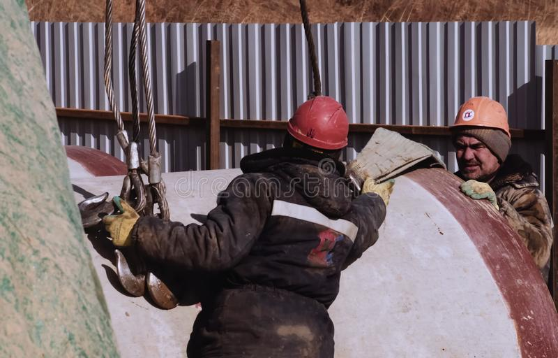 Slinger op het werk Stroplylading Arbeider in een helm royalty-vrije stock afbeeldingen
