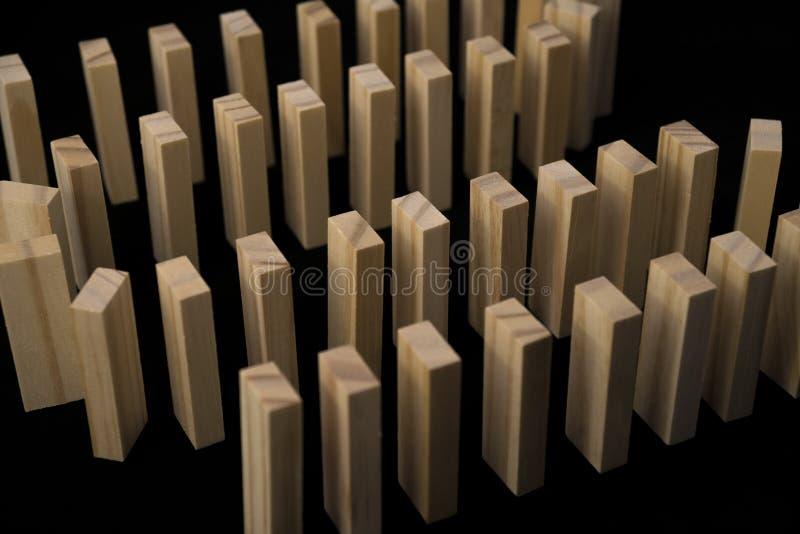 Slingra dominobricka från naturligt trä som är främst av snöbollseffekt, trädominotegelstenar från att smula med hans hand arkivbild
