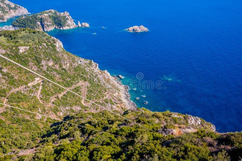 Slingrande väg i berg som täckas med fantastisk sikt för skog från surret, Korfu ö, Grekland blått klart vatten royaltyfria bilder