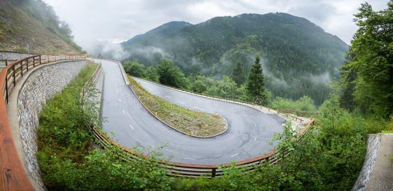 Slingrig bergväg i ett dimmigt vått väder för skog och en hal asfalt Fjällängar Slovenien royaltyfria bilder