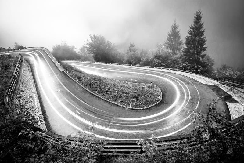 Slingrig bergväg med billjus Dimmigt vått väder och låg synlighet Fjällängar Slovenien arkivbilder