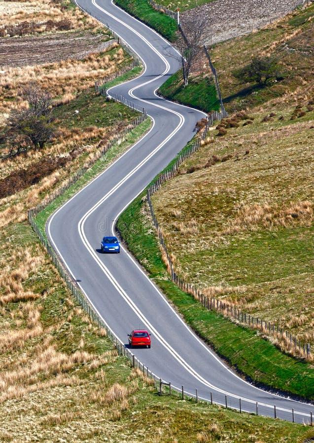 Slingrig väg med bilar arkivbild