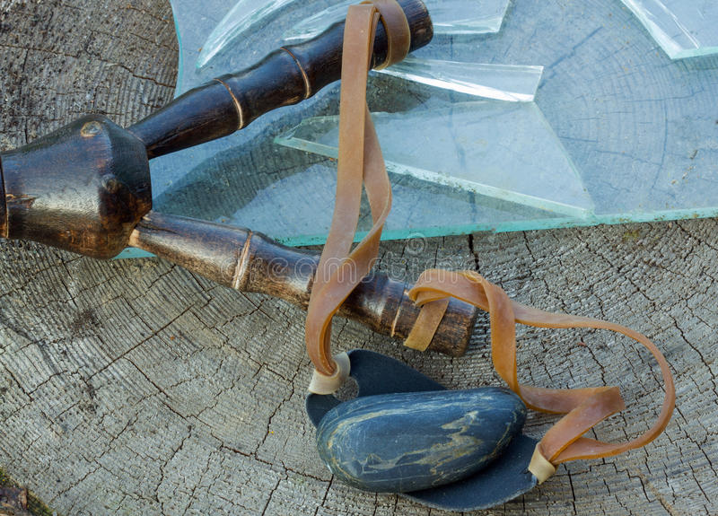 Slingshot,stone and pieces of broken glass. On wooden background stock photo