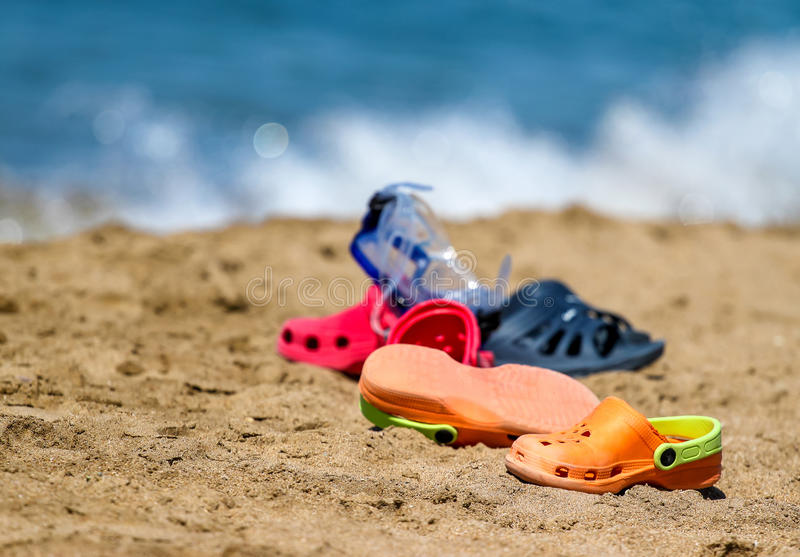 Slippers - kroks and mask on sand beach near the sea water - symbol of summer royalty free stock photography