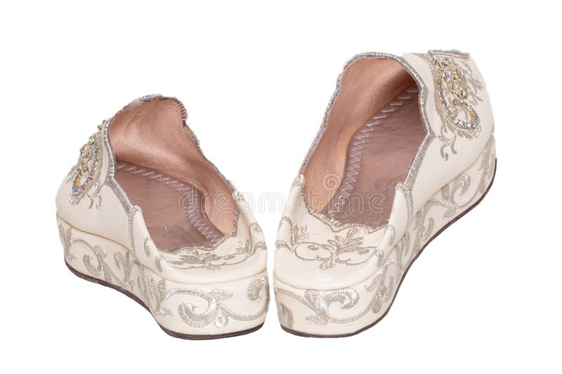 Slippers woman isolated. Closeup of elegant luxurious handmade beige ladies slippers with beautiful floral embroidery and. Rhinestones. Fashionable shoes stock photography