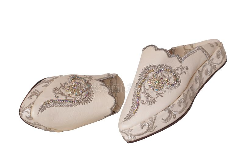 Slippers woman isolated. Closeup of elegant luxurious handmade beige ladies slippers with beautiful floral embroidery and. Rhinestones. Fashionable shoes royalty free stock image