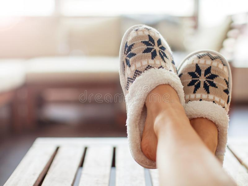 Slippers on women`s legs. Soft comfortable home slipper stock photos